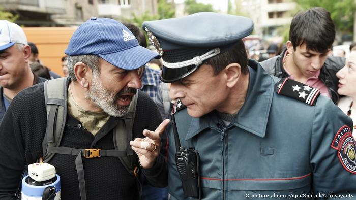 Pashinian speaking to a police officer during mass protests in Yerevan