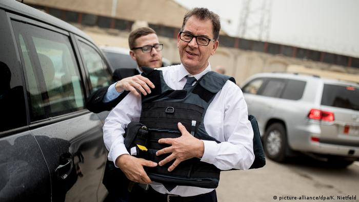 Gerd Müller putting on a bullet-proof vest (picture-alliance/dpa/K. Nietfeld)