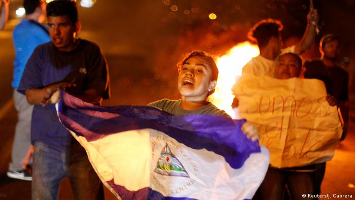 A protester holds up a Nicaraguan flag as a nighttime fire burns in the background.