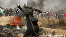 Gaza Grenze zu Israel - Frau wirft steine während Israelische Truppen und Protester aufeinandertreffen