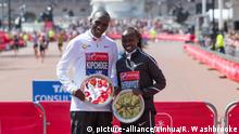 Eliud Kipchoge and Vivian Cheruiyot smiling during the awarding ceremony (picture-alliance/Xinhua/R. Washbrooke)
