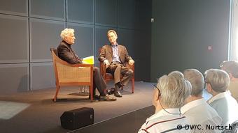 Schlinksits on a chair with an interviewer in front of an audience inSchlossNeuhardenburg
