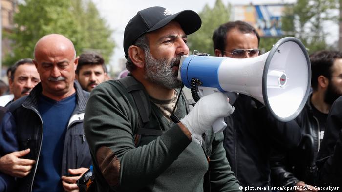 Pashinyan speaking into a megaphone amongst crowd
