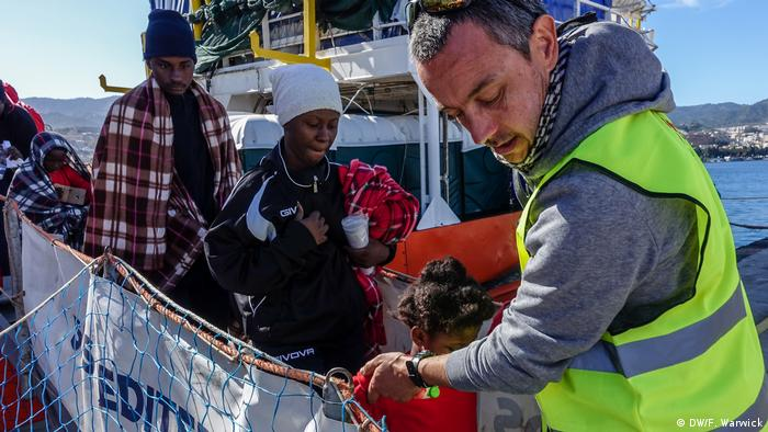 Francois helps men, women and children disembark from the Aquarius (DW/F. Warwick)
