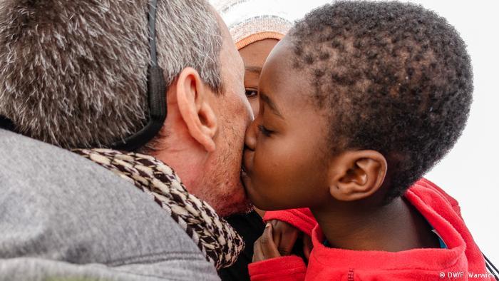 A small boy kisses a man on his cheek (DW/F. Warwick)