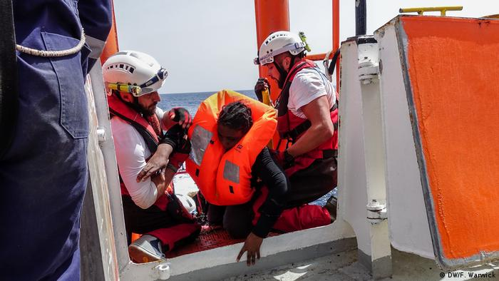 Two men help an exhausted rescued woman on board the Aquarius (DW/F. Warwick)