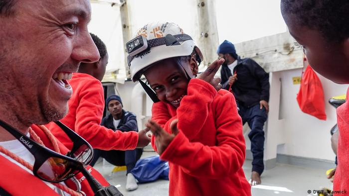 MSF logistician Francois interacts with two children on board the Aquarius (DW/F. Warwick)