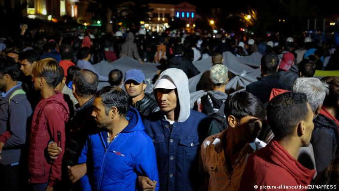 Police separate migrants and right-wing extremists at the island's main port