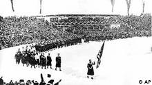 Members of the U.S. Olympic teams march behind the American flag into the ski stadium in the snow during opening ceremonies of the IV Winter Olympic Games in Garmisch-Partenkirchen, Germany, Feb. 6, 1936. There are 668 athletes participating from 28 nations.