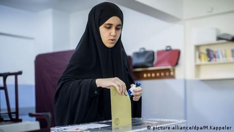 woman wearing a chador at the ballot box (picture-alliance/dpa/M.Kappeler)