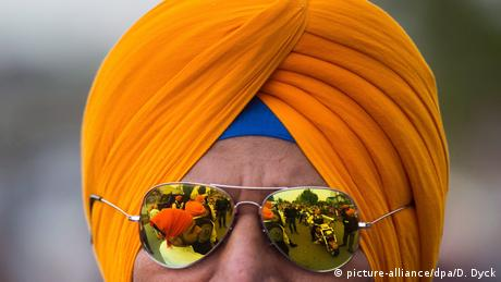 Man wearing an orange Sikh turban (picture-alliance/dpa/D. Dyck)