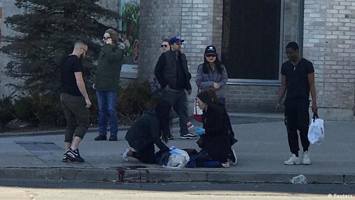 Pedestrians help a victim in Toronto (Reuters)