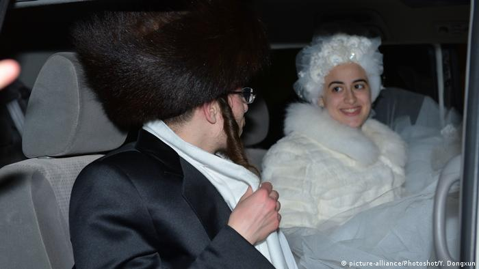 Hasidic man with fur hat and a woman wearing a curly white wig in a car (picture-alliance/Photoshot/Y. Dongxun)