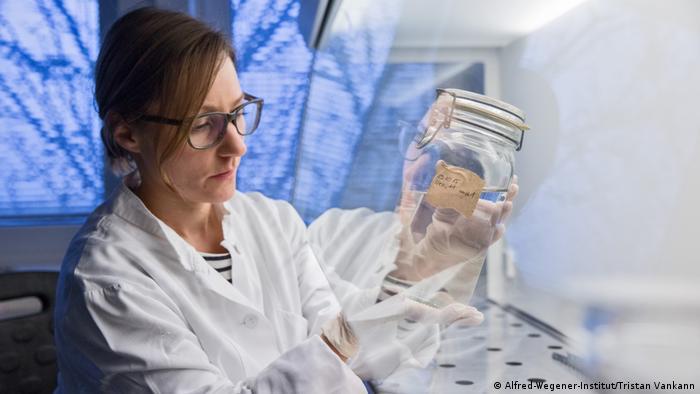 Eine Mitarbeiterin des Alfred-Wegener-Instituts mit einer Meerwasserprobe (Alfred-Wegener-Institut/Tristan Vankann)