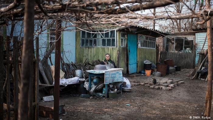 Mulher diante de barraco de madeira na área de exclusão de Chernobyl