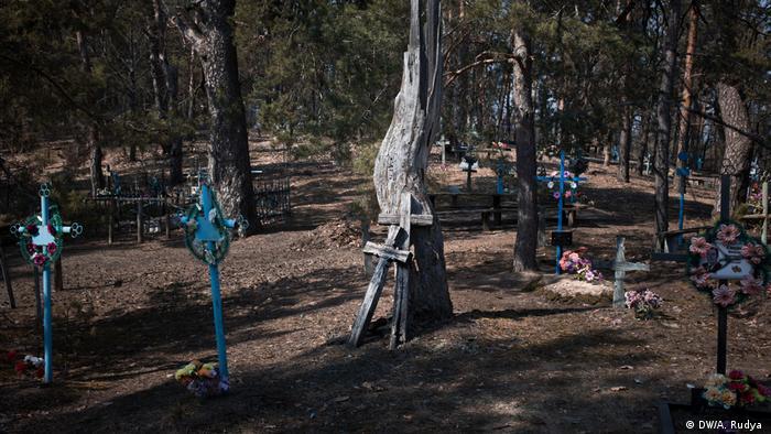 Túmulos e cruzes em Kupuvate, na Ucrânia, na área de exclusão de Chernobyl