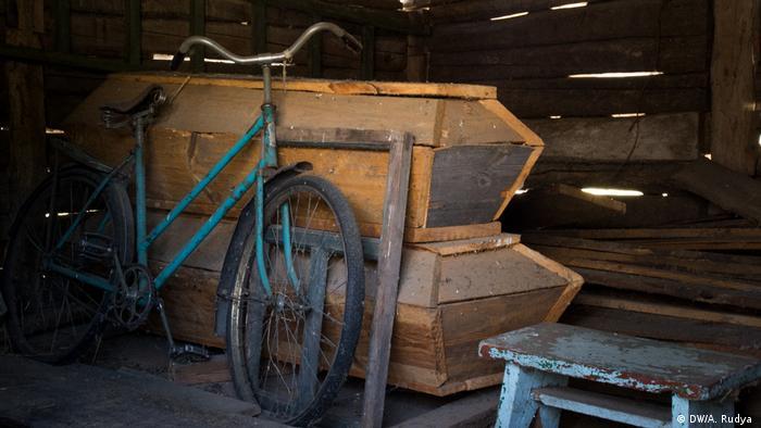 Dois caixões, de Marusia e do marido, Ivan, em galpão ao lado de bicicleta velha