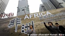 FILE - In this Oct. 26, 2006 file photo, Chinese women stand in front of a billboard which promotes the upcoming China-Africa summit meeting, outside a hotel in Beijing. A new report says on Wednesday, Oct. 11, 2017 that China is closing to matching the United States as a top global source of official grants and loans to developing countries. But it says much of Beijing's financing serves its own economic interests and produces little growth for recipients. (AP Photo/Greg Baker, File) |