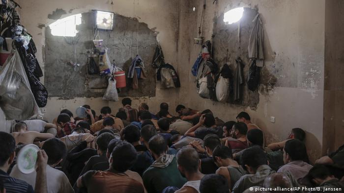 Suspects are crowded into a small room in a prison south of Mosul (picture-alliance/AP Photo/B. Janssen)