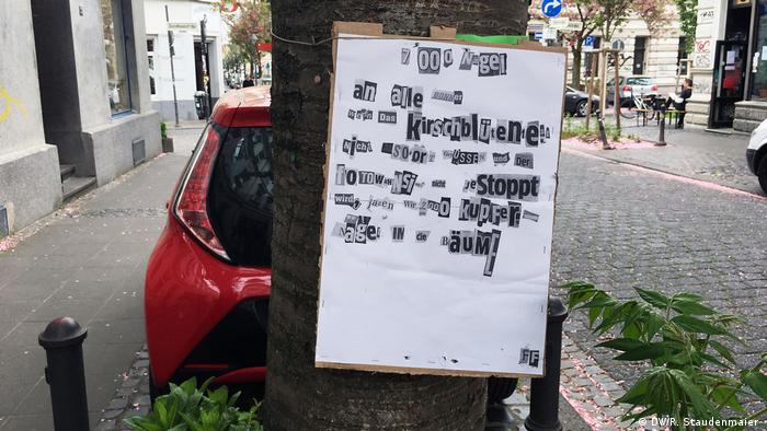 A poster threatening to hammer 7,000 copper nails into Bonn's Japanese cherry blossom hangs on a tree