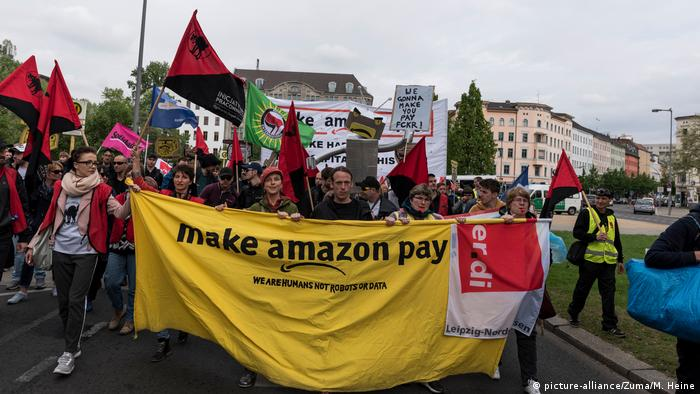 Workers hold up a banner protesting Amazon (picture-alliance/Zuma/M. Heine)