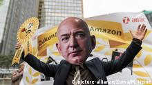 A protester wears a Jeff Bezos mask while standing in front of a banner (picture-alliance/Zuma/M. Heine)