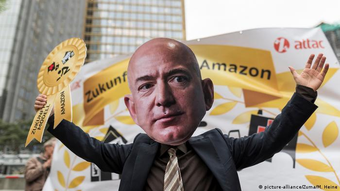 A protester wearing a Jeff Bezos mask holds up a symbolic award while standing in front of a banner (picture-alliance/Zuma/M. Heine)