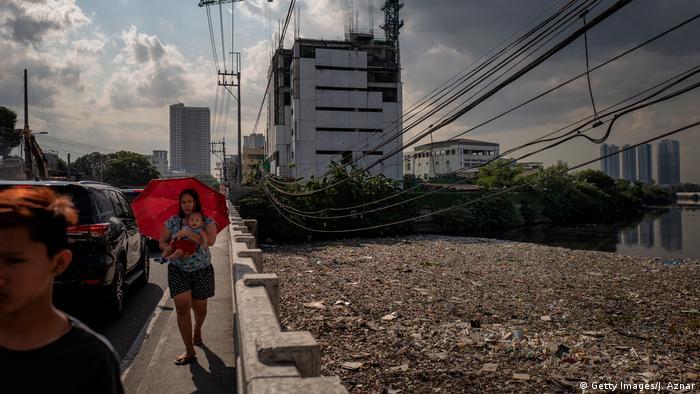 Ein Fluss in der philippinischen Hauptstadt Manila ist voller Plastikmüll. Direkt daneben laufen auf einem Gehweg Menschen. (Foto: Getty Images)