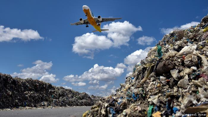 A plane flies over two huge heaps of trash