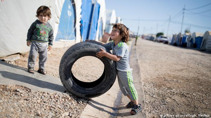 Kids playing with a tire in a refugee camp in Iraq