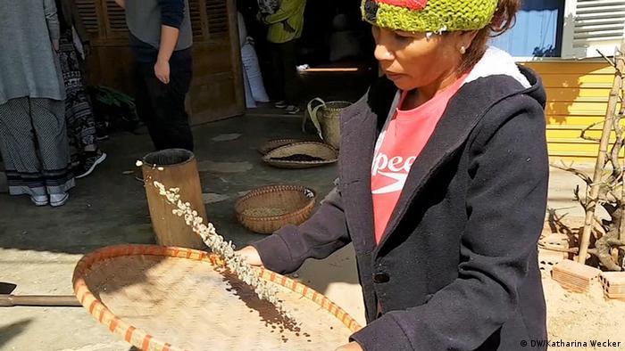 Foto: Eine Frau windsichtet Kaffeebohnen