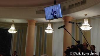 Монитор, на котором виден Олег Навальный за решеткой