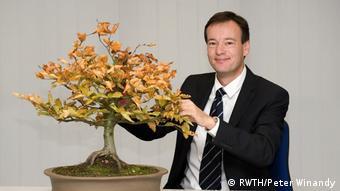 Prof. Manfred ChristianWirsum tending a bonsai tree.