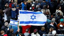 An Israeli flag is held during a demonstration in front of a Jewish synagogue, to denounce an anti-Semitic attack on a young man wearing a kippa in the capital earlier this month, in Berlin, Germany, April 25, 2018. REUTERS/Fabrizio Bensch