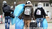 Flüchtlingen tragen am 22.12.2014 in Heidelberg (Baden-Württemberg) in einer Flüchtlingsunterkunft auf dem Gelände des Patrick-Henry-Village nach ihrer Ankunft ihr Gepäck zu den Unterkünften. Foto: Uwe Anspach/dpa  