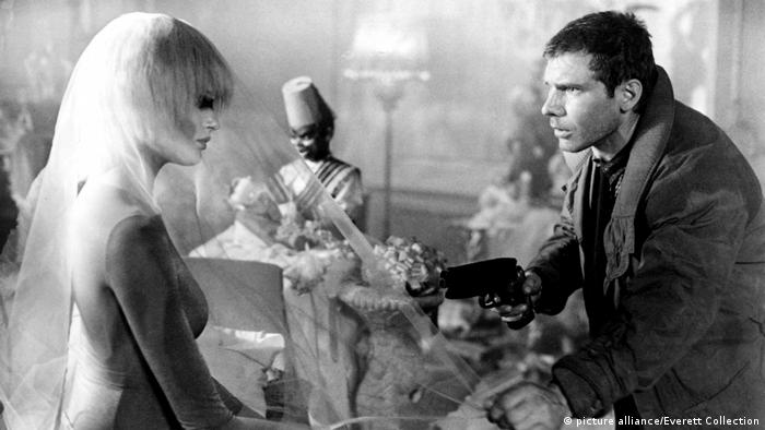 Rick Deckard (Harrison Ford) richtet in Blade Runner auf eine Replikantin. (picture alliance/Everett Collection)