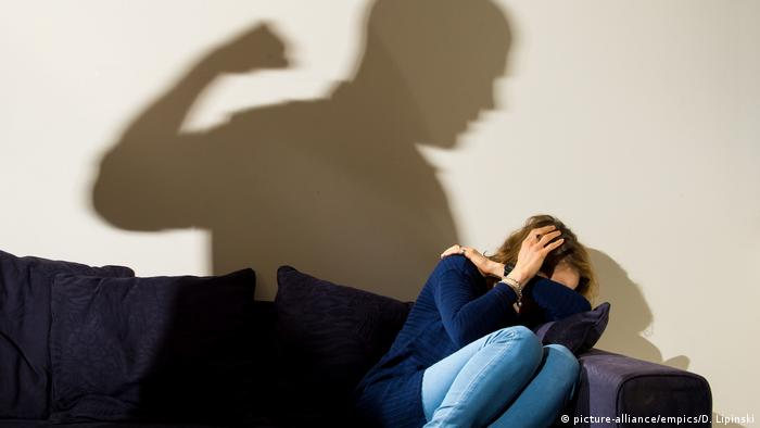A shadow of a man with a clenched fist threatening a cowering woman