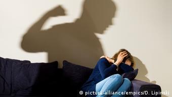 Женщина сидит на диване, сжавшись, на стене - тень мужчины, занесшего над ней руку