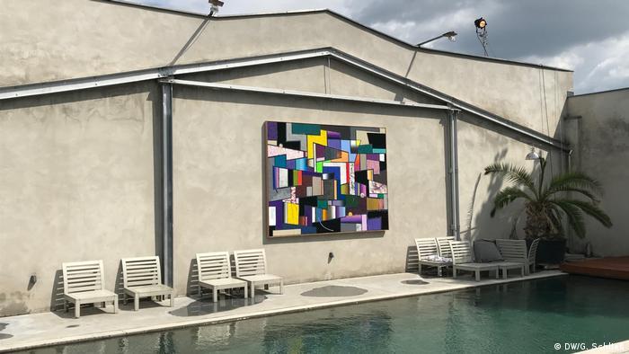 Ein buntes Bild von Christian Achenbach, das in der Nähe des Pools hängt, Foto: Schließ