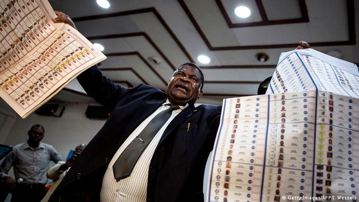 An election official holds up two large sheets of paper with a long list of candidates vying for office