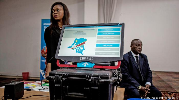 A voting machine in DR Congo, with two CENI officials in the background