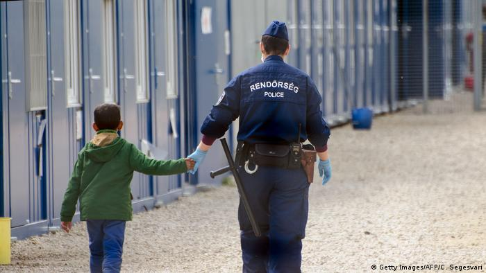 A child being led by the hand in a Hungarian transit center (Getty Images/AFP/C. Segesvari)