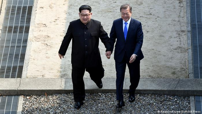 Kim and Moon walking hand-in-hand