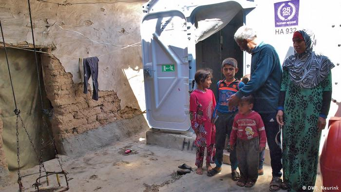 An Iraqi family in their partially destroyed house