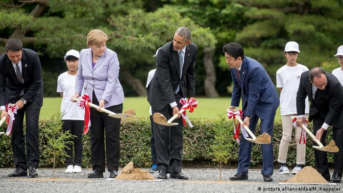 German Chancellor Angela Merkel plants a tree in Ise-Shima, Japan, next to former US President Barack Obama