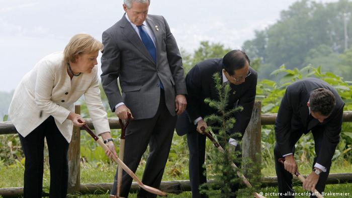 German Chancellor Angela Merkel plants a tree next to former US President George W. Bush
