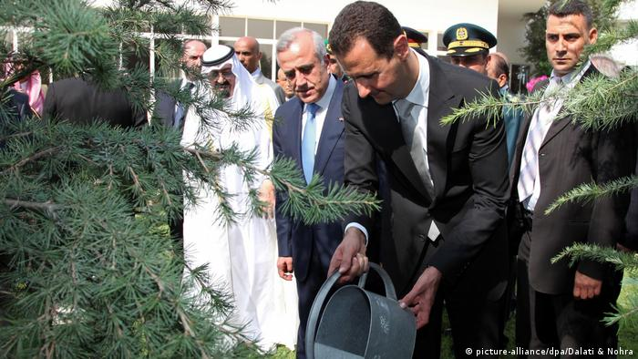 Syrian President Bashar Assad watering a tree next to the late Saudi King Abdullah