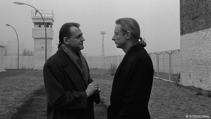 two men stand by the Berlin wall with a watch tower behind (STUDIOCANAL)