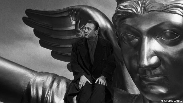 Ator Bruno Ganz sentado no ombro de um anjo metálico, em cena do filme Asas do desejo