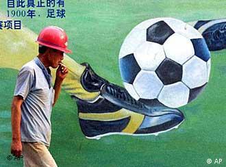 Kineski radnik u Pekingu s plakatom na kojem je nogometna lopta